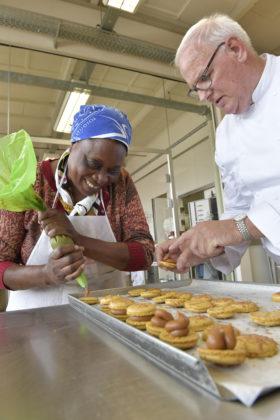 Agnes Temu kan niet genoeg krijgen van het leren. Zij neemt de kennis mee naar huis om in de bakkerij bij de school waarvan zij directeur is in de praktijk te brengen. PUM-begeleider Leo van den Berg geeft aanwijzingen.